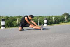 Male runners are stretching the leg muscles to prepare for a run Stock Photo