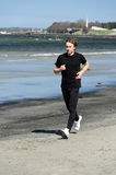 Male running on the beach. Athletic young male running on the beach Royalty Free Stock Image