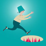 Male running with a bucket head. Unseen pitfall ahead. Royalty Free Stock Image