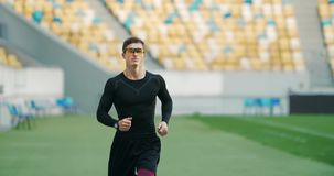 Male Running on Stadium. Handsome young male athlete in black outfit and eyeglasses running on stadium, preparing for competition stock video
