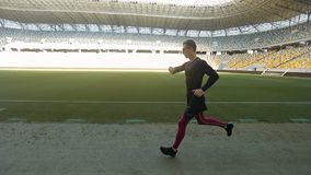 Male Running on Stadium. Side view of young male athlete in black outfit and eyeglasses running on stadium stock video footage