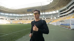 Male Running on Stadium. Young male athlete in black outfit and eyeglasses running on stadium stock video footage