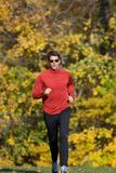 Male Running Towards Camera. Young male running outdoors in a park. Fully body shot. Wearing red shirt and black pants. There are yellow and green trees gently Stock Images