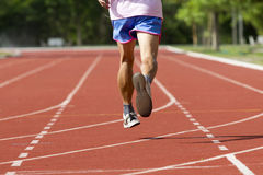 Male running at a track and field Stock Photo