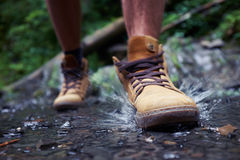 Male`s boots with splashing water. Close-up of males boots with splashing water Royalty Free Stock Photography