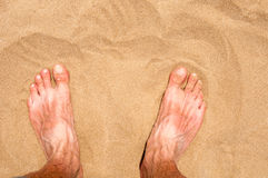 Male`s foot on sand. Close up Royalty Free Stock Photos