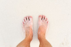 Male`s foot on sand. Man's legs on the white sand Indian ocean Stock Image