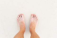 Male`s foot on sand. Man`s legs on the white sand Indian ocean Stock Photo