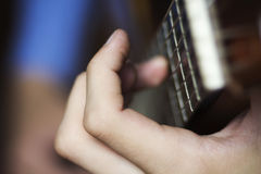 Male's hand on a classical guitar fretboard Stock Image