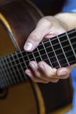 Male's hand on a classical guitar fretboard Stock Images