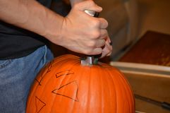 A male`s hand cutting the top off of a jack-o-lantern royalty free stock photo