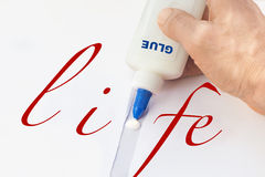 Male's hand fixing with glue broken word life. On a white paper Stock Photography