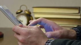 Male`s hand holding digital tablet with book stack on the desk stock video