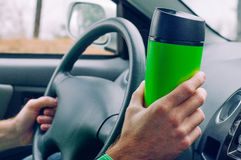 Male`s hand holding thermo mug with coffee. Close up of male`s hand holding thermo mug with hot coffee driving a car Royalty Free Stock Image
