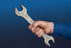 Male's hand with a wrench. Close view of a male's hand with a wrench in a blue background Stock Images