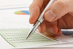 Male�s hand writing in the document. Male hand is writing in business document lying on the table Stock Photo