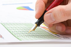 Male�s hand writing in the document. Male hand is writing in business document lying on the table Stock Images