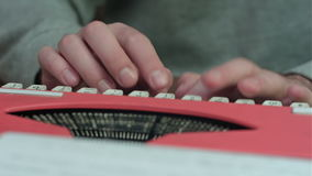 Male`s hands typing on a red typing machine. Close up shot. Professional shot on BMCC RAW with high dynamic range. You can use it e.g. in your commercial video stock footage