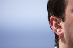 Male's Hearing Aid. Shot of a Man's Hearing Aid against a Blue Background of Sea and Sky Stock Photos