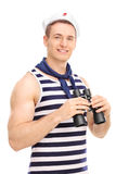 Male sailor holding binoculars and smiling Stock Image