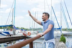 Male sailor waving up on pier and smiling. Yachtsman gives the command by hand to moor in dock. Man welcomes newcoming boat. Young sailor waving up on pier with Stock Images