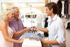 Male Sales Assistant At Checkout Of Store. Male Sales Assistant At Checkout Of Clothing Store With Customers Royalty Free Stock Images