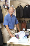 Male sales assistant in clothing store. Looking relaxed and cheerful Stock Photography