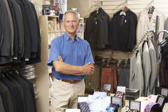 Male sales assistant in clothing store. With arms crossed Stock Photos