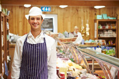 Male Sales Assistant In Delicatessen. Smiling To Camera Royalty Free Stock Photography