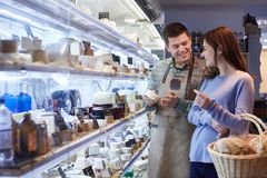 Male Sales Assistant Giving Advice To Female Customer In Delicatessen Shopping For Cheese royalty free stock images