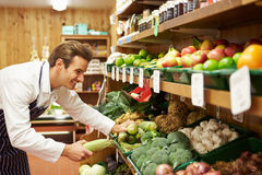 Male Sales Assistant At Vegetable Counter Of Farm Shop Stock Photo