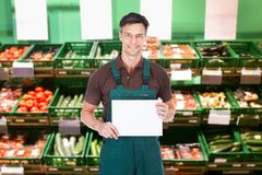 Male sales clerk holding a placard. Mature Male Sales Clerk Holding A Blank Placard In Supermarket Stock Photography