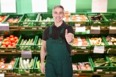 Male sales clerk showing thumb up gesture. Mature Male Sales Clerk Showing Thumb Up Gesture In Supermarket Royalty Free Stock Photos
