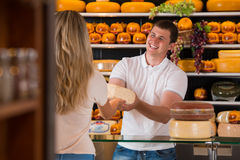 Male salesman in cheese store with a female customer. Talking about his products and helping to choose delicious cheese Stock Photography