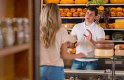 Male salesman in cheese store with a female customer. Talking about his products and helping to choose delicious cheese Royalty Free Stock Image