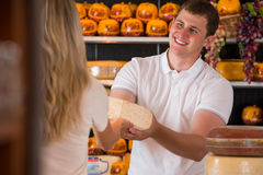 Male salesman in cheese store with a female customer. Talking about his products and helping to choose delicious cheese Stock Image