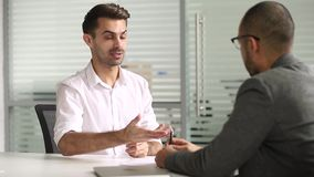 Male salesman talking with client handshaking closing deal at meeting