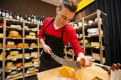 Male salesperson cutting cheese in store Royalty Free Stock Images