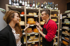 Male salesperson showing cheese to female customer in store Royalty Free Stock Photos