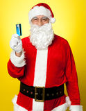 Male in Santa costume posing with his cash card. Lets go shopping Royalty Free Stock Photography