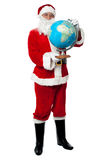 Male santa holding a globe map Royalty Free Stock Image