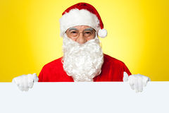 Male Santa standing behind big blank banner. Ad board. Business concept Stock Photo
