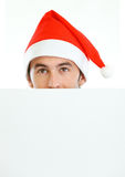 Male in Santas hat hiding behind blank billboard. Isolated on white Royalty Free Stock Photography