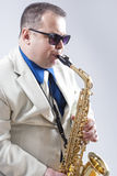 Male Saxo Player in Sunglasses Performing Expressively in Studio. Vertical Image Orientation Stock Photography