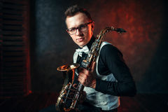 Male saxophonist with saxophone, jazz man with sax. Portrait of male saxophonist with saxophone, jazz man with sax. Classical brass band instrument Stock Image