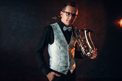 Male saxophonist with saxophone, jazz man with sax. Portrait of male saxophonist with saxophone, jazz man with sax. Classical brass band instrument Royalty Free Stock Photos