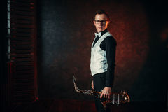 Male saxophonist with saxophone, jazz man with sax. Portrait of male saxophonist with saxophone, jazz man with sax. Classical brass band instrument Stock Photography