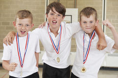 Male School Sports Team In Gym With Medals Stock Photo