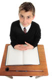 Male school student looking up. A young male school student in uniform looking up from desk.  Above view Stock Images