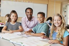 Male school teacher and kids in class smiling to camera royalty free stock photography